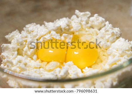 Cottage cheese and two eggs close-up. Raw Ingredients in bowl. Ingredients for homemade cheesecake or baking #796098631