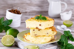Cottage cheese casserole with raisins and mint, lime slices on a plate on a white wooden table