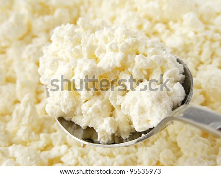 Cottage cheese clods and spoon. Macro image.