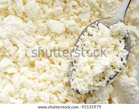 Cottage cheese clods with spoon. Macro image.