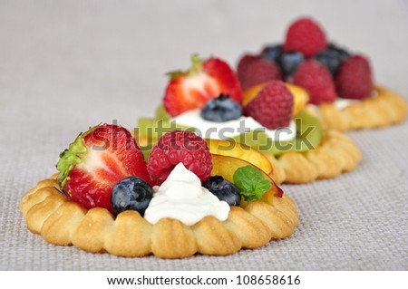 Cottage cheese cream tarts with a slices of berries and fruits
