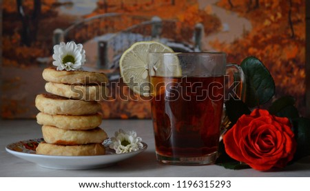 Cottage cheese healthy pancakes with wlolemeal flour, a glass of black tea with a slice of lemon decorated with small white flowers and a fresh red roese on the backgroung of an autumn forest painting