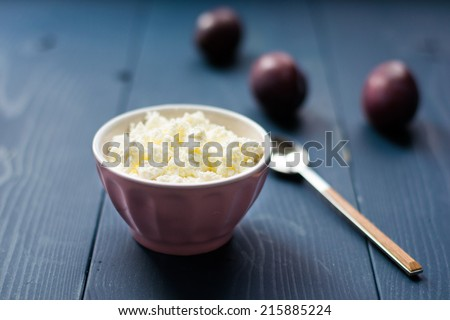 Cottage cheese in a bowl on a wooden table
