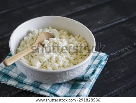 cottage cheese in a white bowl on a dark wooden background