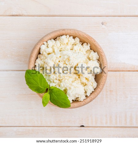 cottage cheese in a wooden bowl on a wooden background