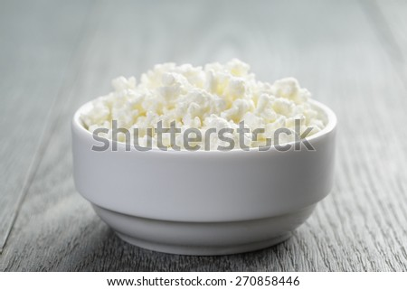 cottage cheese in white bowl on old table