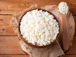 Cottage cheese on a wooden stand. Cottage cheese in a bowl. Soft cheese and wooden spoon on a wooden boards