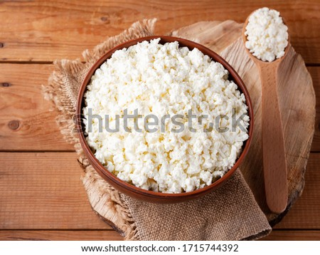 Photo of  Cottage cheese on a wooden stand. Cottage cheese in a bowl. Soft cheese and wooden spoon on a wooden boards