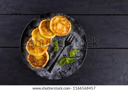 Cottage cheese pancakes on a dark background. Syrniki with fresh mint. Pancakes with cottage cheese on a black plate sprinkled with powdered sugar. Homemade food