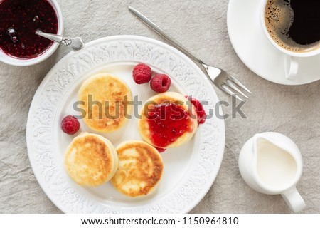 Cottage cheese pancakes with jam and coffee. Russian syrniki or sirniki, cottage cheese fritters or pancakes served with raspberry jam and cup of coffee