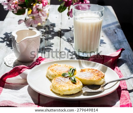 cottage cheese pancakes with mint and powdered sugar, flowers, a glass of milk and honey, breakfast