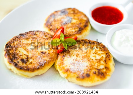 Cottage cheese pancakes with sour cream and strawberry sauce