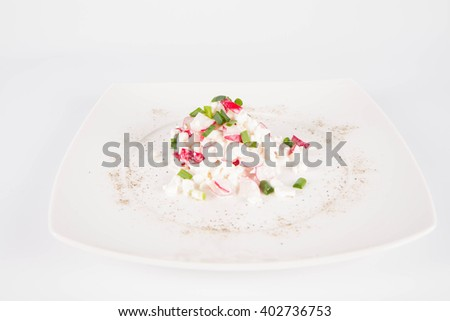 Cottage cheese with radish and chives on a white plate