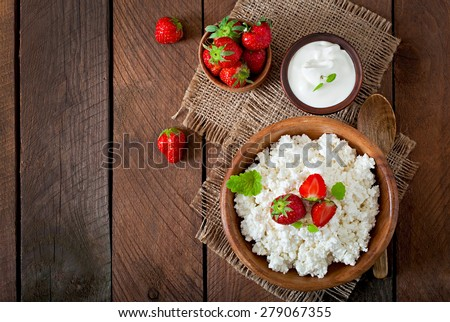 Cottage cheese with strawberries in a wooden bowl.  Top view