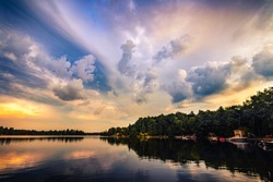 COTTAGE LAKE IN CANADA - Beautiful sunrise/sunset clouds over a lake at a cottage. Quiet, peaceful, serene scene with boats in water and houses on lakefront. Gorgeous clouds in sky. Muskoka, Canada