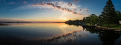 Cottage lake in Canada - Beautiful sunrise/sunset clouds reflecting in a lake at a cottage. Quiet, peaceful, serene. Gorgeous clouds in sky. Balsam Lake Kawartha Lakes, Canada