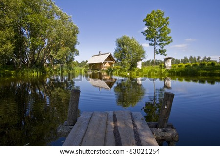 Cottage near pond with reflection in water, located in Latvia