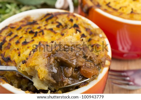 Cottage Pie - Individual cottage pies on a wooden surface. Close up.