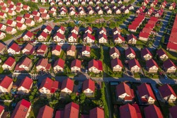 Cottage village top view. Lots of houses with red roofs. Panorama of catedge village, top view. Suburban area with same houses. Panorama of suburbia. Small residential buildings with lawns.