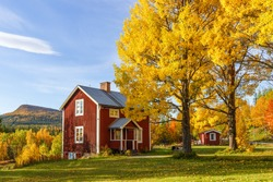 Cottage with garden with autumn colors in a mountain landscape