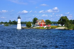 Cottage with lighthouse on one of the Thousand Islands during summer, New York state, USA