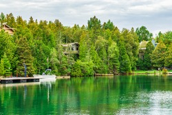 Cottages by Lake Huron shoreline surrounded by century old cedar trees on sunny summer day