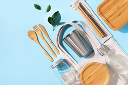 Cotton bags, glass jar, bottle, metal cup, straws for drinking, bamboo cutlery and boxes on blue background. Sustainable lifestyle. Zero waste, plastic free shopping concept.