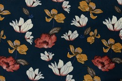 Cotton fabric with folds, white red yellow flowers and green leaves pattern on blue background. Fragment of cloth with a pattern colorful flower textile pattern with floral ornament