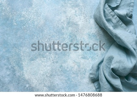 Cotton kitchen napkin or towel over light blue slate, stone or concrete table.Copy space background.