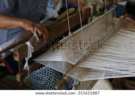 cotton on the manual wood loom in Asian traditional culture and woman lifestyle ,Weaving shuttle on the warp, Weaving loom and shuttle on the warp. fashion fabric factory and business in Thailand. #315651887