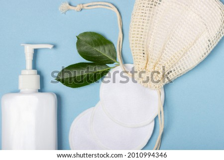 Cotton reusable make-up remover pads in a cloth bag and face wash and cleanser on a blue background. The concept of ecology and conscious consumption. Reusable cotton pads Foto stock ©