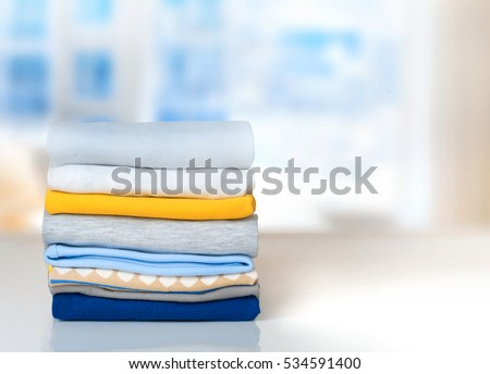 Cotton stack of colorful folded clothes on white table indoors empty space background.Household concept.Clean laundry pile.