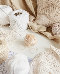 Cotton thread and hook on a table surrounded by beige cotton balls and doilies