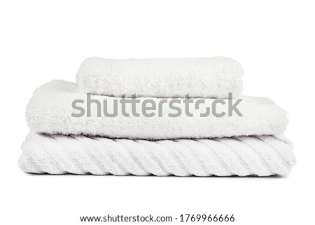 Cotton towels neatly folded. Shower towel in different sizes. White fabric towels for washing. Production of bath accessories. Production belongings for swimming. Textile towels white background