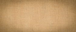 cotton woven fabric background with flecks of varying colors of beige and brown. with copy space.  Hessian sackcloth burlap woven texture background