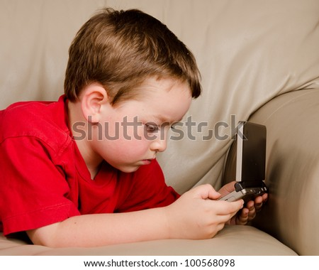 Couch potato concept of boy playing video game while resting on sofa