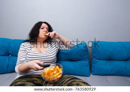 Couch potato overweight woman sitting on the sofa, eating chips while watching TV. Sedentary lifestyle, bad habits, eating disorder concept