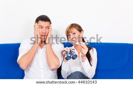 Couch sitting couple with positive pregnant test while man is very surprised and shocked , is female happy looking in camera