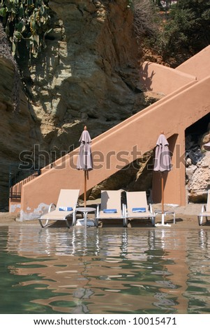 couches and sunshade at sea coast with reflection in water - stock photo