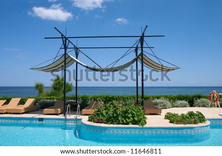 couches and sunshade near swimming pool on the sea coast