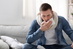 Cough fit. Young covid-19 infected man coughing at home, empty space