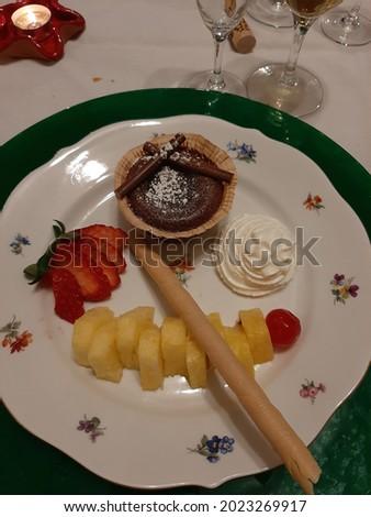 Coulant chocolate negro acompañado de fresa ligeramente cortada, trozo de piña muy dulce con frambuesas y coronada con montañita de nata y barquillo relleno de turrón para celebraciones y fiestas Foto stock ©