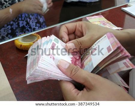 Count Indonesian rupiah money Rp.100,000 with hand in money changer, Kuta, Bali