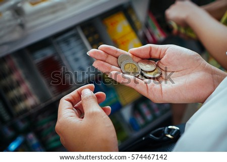 Count Thai coin in hand for shopping snack in convenient store