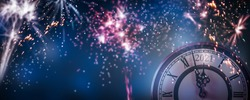 countdown new years eve 2021 with colorful fireworks on dark blue sky background, clock and blurred firecrackers  for happy new year celebration, explosion light effects