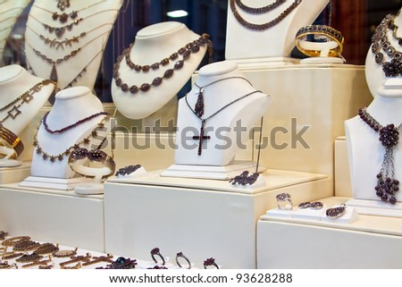 counter with garnet jewelry in store window