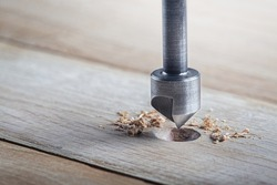 Countersink drill bit make sink in hole for screw in wooden plank.