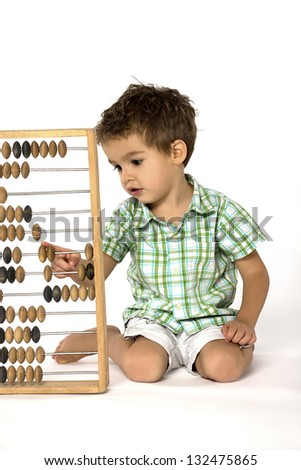 Counting little boy with abacus - stock photo