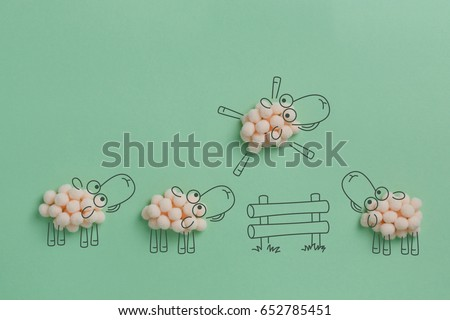 Counting sheep made of cotton balls jumping over the fence. Creative concept of mixing real objects and computer graphic.