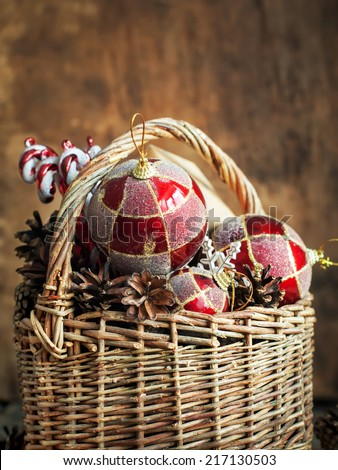 Country Christmas Composition with gifts. Basket, red balls, pine cones, sweets. Vintage style
